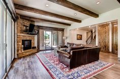 Large finished basement that opens out onto a cover patio. Rustic open floor plan with corner fireplace and media center, and exposed wood beams