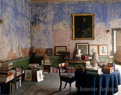 The walls of this dilapidated yet stylish makeshift library in a Georgian townhouse in Dublin reveal the shade of blue in which the room was originally painted