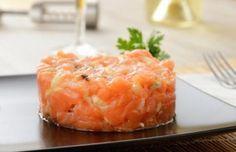 Tartar de salmón Para 2 persdonas: Quitar la piel del salmón y cortarlo en dadidos pequeños. En un bol poner el salmón cortado y salar. Añadir el zumo de media lima y el aceite de oliva extra virgen. Mezclar todos los ingredientes y macerar en la nevera durante 2 horas mínimo. Añadir la cebolleta cortada en trozos muy pequeños, la pimienta negra y un poco de salsa de soja. Mezclar bien todos los ingredientes. Servir en un plato y decorar con alcaparras por encima y el eneldo.