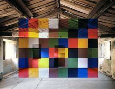 George Rousse, La flêche, 1993. Georges Rousse (born 1947 in Paris) is a French photographer.  Rousse's work, from the 1990s to today, generally appears at first glance to be photos of desolate or abandoned spaces (buildings, rooms, parking garages or street scapes) often on their way to the wrecking ball, on which the artist has superimposed precise geometrical shapes or squiggly graffiti.