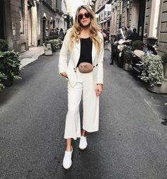 Blazer, pantalones y zapatos blancos, combinados con una blusa negra, un bolso de cintura, y unos anteojos grandes en rojo. Complementa lo formal con lo informal en esta combinación perfecta para las calles.