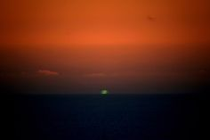 Green Flash: Blink and you'll miss it!  The last instant before the sun sets in right conditions the sun light turns into a green flash.  Happens when sunset is on a water horizon.  Seen a lot from California beaches sunsets.