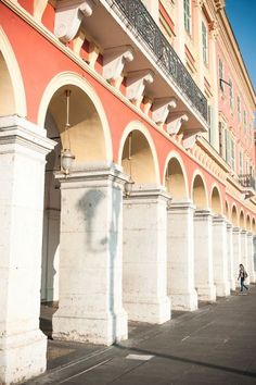 The shadow of streetlights created by a morning sun rises on one of the arches of the place massena.