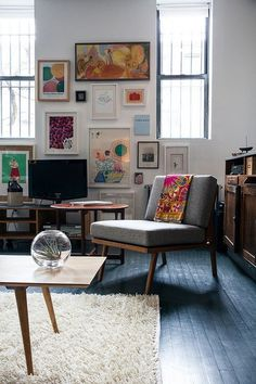 Splashes of colour, slightly bohemian living space but clean with white walls and dark wooden floors.