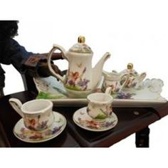 $29.99 Fairy Fantasy Fine China Tea Set. Nothing could be prettier than this fine quality miniature porcelain tea set scaled just right for use with collectible dolls or tea set collections. This tea set includes a porcelain tray, teapot, sugar and creamer set, and 2 cups and saucers. All are attractively stored in a burgundy colored satin lined gift box for safe-keeping. Tea pot measures 3.5 in. H. Tray measures 4.5 x 9.5 in. Also sold separately is our EXCLUSIVE doll-size tea cart.