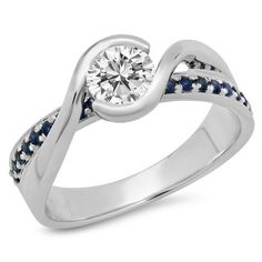 Swirling and sophisticated, this engagement ring is just her stunning style. Created in 10K White Gold, the engagement ring features a sparkling 0.72 ct. white diamond center stone. Smaller accent heated blue sapphire-lined gracefully bypassing shank wraps this center stone in a sparkling embrace. Radiant with 1.00 ct. of stones, this ring is a brilliant beginning to a lifetime of love. Dazzling rock offers you more than any other jeweler, ever.