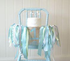Smash Cake High Chair Decor Ideas - love this ribbon garland and baby blue wooden high chair for a first birthday!