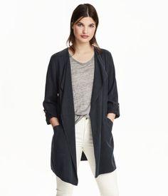 Lange Jacke aus weicher Tencel® Lyocell-Mischung. Die Jacke hat ein drapiertes Revers, Vordertaschen und lange Ärmel mit Druckknopfriegel zum Umschlagen. Ungefüttert.