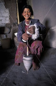 Ladakhi woman spinning wool with a drop spindle, near Leh, Ladakh, Jammu and Kashmir, India.