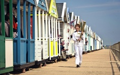 A torchbearer carries the Olympic Flame in front of the beach huts at Southwold, southeast England during Day 48 of the London 2012 Olympic Torch Relay. (AP/LOCOG)