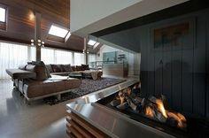 salon moderne avec cheminéе, canapé en cuir marron et tapis à poil long gris