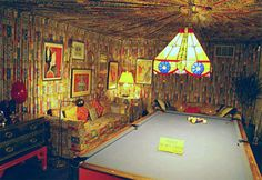 billiard room in the basement. the walls and couches are matching fabric