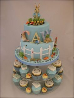 Little Cakes Peter Rabbit cake with matching cupcakes, storybook, Peter Rabbit, with white picket fencing. carrots, blue