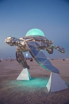 """Cosmic Voyager - Martin Taylor/ Chromaforms - Cosmic Voyager combines the ancient mytheme of the """"Cosmic Turtle,"""" carrying the world on its back, with reflective futuristic design reminiscent of a """"Spaceship Earth"""" traveling through space. Futuristic Design, Futuristic City, Burning Man Art, Polygon Art, Public Art, Interactive Art, Art Festival, Beach Art, Urban Art"""