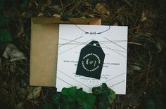 A craft paper envelope and navy tag gives this simple white invitation a rustic twist. Photo: Dixie Pixel