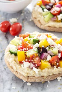 Bright, flavorful, and healthy mini pita pizzas! These pizzas are topped with hummus and the most delicious Greek salad!