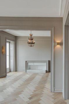 Neutral interior design with herringbone floors, contemporary marble fireplace, and beige walls. Design by Cristina Jorge de Carvalho. Photo by João Morgado. #ModernHomeDecorInteriorDesign