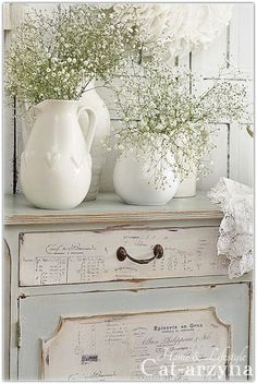 This is beautiful and has all the things I love. Ephemera, white pitchers, babies breath, lace, and old furniture with character.