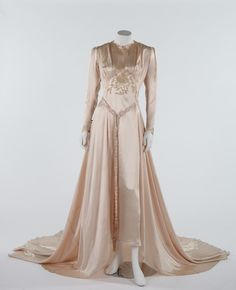 The pink satin wedding gown worn by Joyce Meriel Palfret, 22nd September 1945. for her marriage to Staff Sergeant Geoffrey Hunt RASC, with ecru chainstitch embroidery to the bodice and long trained skirt, bust approx 97cm, 38in, with plaited belt, photographs of the bride on the day, veil, honeymoon hotel receipt and invitation