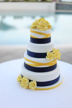 wedding cake- Four circle shaped tiers with white icing, navy blue icing ribbon at the bottom of each layer, yellow icing ribbon on every other tier, and yellow roses on the top, middle, and bottom tiers