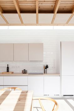 Inside this modern house extension is a kitchen with white and tan cabinets that's positioned along the wall, while white tiles help to reflect the light from the skylight above the kitchen.
