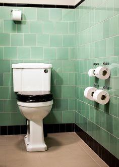 Toalett med kakel i Vicarage green med en svart fris av Albert. Väggarna är målade med väggfärg från Auro i kulören Koala. Spegeln är ställbar med fästen av förkromad mässing. Diameter: 511 mm. Bygger 75 mm ut från vägg.