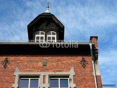 Dachgaube mit Sprossenfenster und schönem Giebel auf der Backsteinfassade der alten Schule