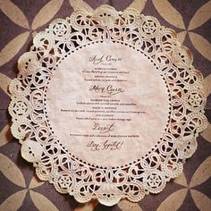 Creative wedding menus: White paper doilies purchased in bulk were stained with tea for a vintage look; after drying, each doily was stamped with the menu text using a custom rubber stamp and then pressed flat with an iron.