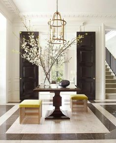 Elegant, contemporary and a touch of glam in this entry way interior design with giant black wood doors