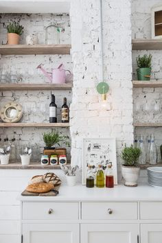 white masonary brick wall is giving a retro look to the kitchen + open shelving