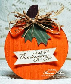 handmade Thanksgiving card from Stamping with Klass ... round card format ... pumpkin design ... lots of texture ... embossing folder ragged lines on pumpkin surface, corrugated paper leaves ... roughed edges on sentiment banner ... raffia and crinkled package filler ... great card!!