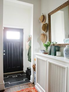 A vintage gold mirror hangs above an entry table created from the custom radiator cover in this eclectic home's entryway. Pops of color are added with the vibrant antique rug and accessories while the black door and custom black and white tile work add sophistication to the space.