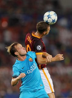 Edin Dzeko (R) of AS Roma competes for the ball with Ivan Rakitic of FC Barcelona during the UEFA Champions League Group E match between AS Roma and FC Barcelona at Stadio Olimpico on September 16, 2015 in Rome, Italy.