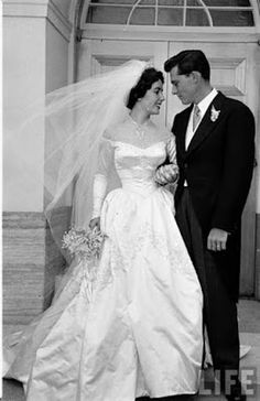 """Elizabeth Taylor's first wedding dress, designed by the legendary costume designer Helen Rose.  Worn for Taylor's wedding to Conrad """"Nicky"""" Hilton, Jr. in 1950. Twenty five yards of shell-white satin embellished with bugle beads & seed pearls, trailed by fifteen-yards of satin train. A built-in corset allowed the dress to be tightly cinched in at the waist. The veil's ten yards of shimmering silk net was attached to a pearl-covered Juliet cap in order to float around Elizabeth."""