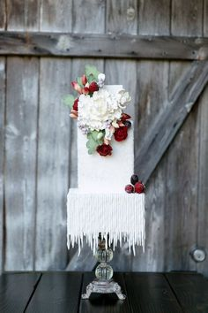 10 Winter Wedding Cakes That Creatively Ice Out Their Competition | A chic wedding cake with icicle inspired frosting and detailed floral decorations.