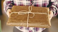 A man holding a brown paper wrapped gift