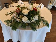 With evergreen greenery, red berries and white roses.