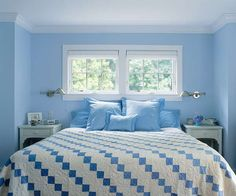 Coordinated blue and white bedding and furniture pair well with the cool blue walls and awning-style windows that open to allow fresh breezes. | Photo: Julian Wass | thisoldhouse.com