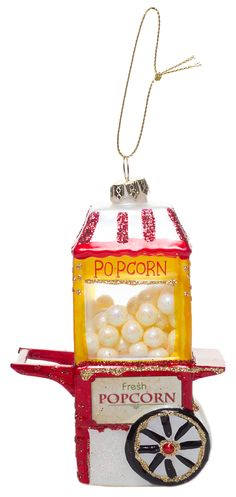 POPCORN MACHINE XMAS ORNAMENT - Remember when the vendors would come to you with their rolling carts? No me neither! This glass Christmas ornament with glitter details features a popcorn machine used by vendors of an earlier era. There are even some popcorn balls inside that move around!
