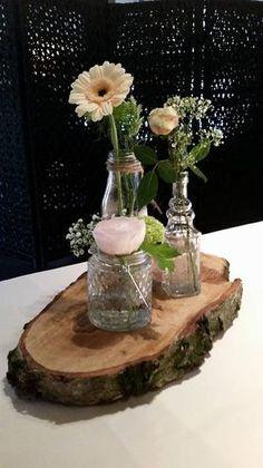 Boomschijf als decoratie plankje, met daarop kleine flesje met verse bloemen. Boomschijven verkrijgbaar op webshop Decoratietakken