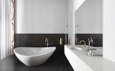 Black and white bathroom with an original white bathtub.  Salle de bain confortable et moderne noir et blanc avec une baignoire de forme originale.   By New Home Agency