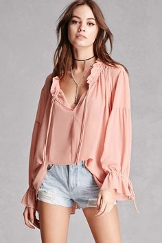 A crepe woven top featuring a ruffled self-tie neckline, long puff sleeves with self-ties, and a billowy silhouette. This is an independent brand and not a Forever 21 branded item.