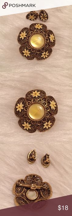 Vintage Brooch & Matching Earrings Yellow & gold flower pin with matching clip on earrings. The center yellow stone has some hairline cracks through it but it smooth to the touch and will not come apart. Very cute vintage set! Vintage Jewelry Brooches