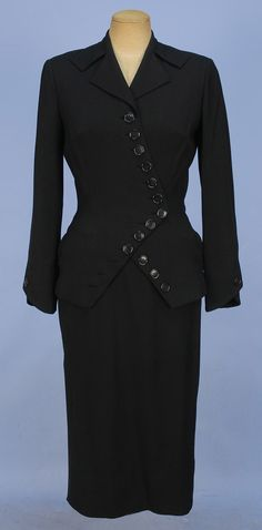 IRENE WOOL SUIT with ZIG-ZAG BUTTONS, 1950's. Black with deep notched lapel and asymmetrical button closure, angled sleeve with single button, side slit pockets, skirt with diagonal front seam and side slit.