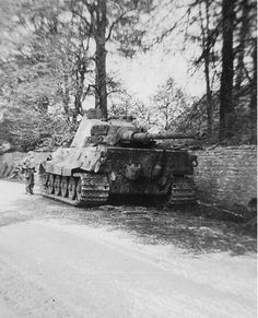 A lone GI looks at an intact and abandoned King Tiger that likely ran out of fuel during it's retreat back into German occupied territory