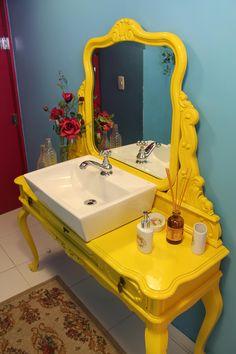 A penteadeira antiga foi transformada em um lavatório para o banheiro.