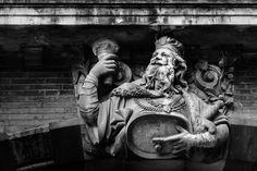 Cette statue représente Gambrinus, le Roi de la bière. D'après une légende flamande, il aurait obtenu ce titre royal en inventant la bière grâce à un pacte signé avec le diable pour oublier un amour à sens unique. C'est au-dessus du porche du 10 bis rue du Pont de Tounis, à l'emplacement d'une ancienne brasserie tenue par un alsacien venu s'installer à Toulouse en 1871 pour fuir la guerre franco-prussienne, que Gambrinus lève son verre aux noctambules toulousains.