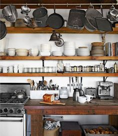 Kitchen with lots of shelves for pots, pans, cups, dishes and cooking utensils. Very rustic.