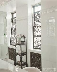 Fretwork panels screening master bathroom windows featured in Elle Decor