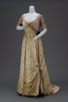 Evening dress        American, about 1915         United States  Dimensions      132 x 88 cm (51 15/16 x 34 5/8 in.)  Medium or Technique      Silk satin and gold-colored metallic warppped thread brocade, silk taffeta, silk satin, gold-colored metallic wrapped thread net, gold-colored metallic wrapped thread with white-colored rhinestones net, taffeta (synthetic?), net (synthetic?), metal and rhinestone ornament and metal closures  Classification      Costumes     Accession Number…